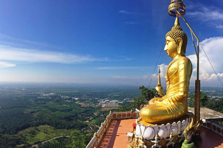 Groot goudkleurig Boeddhabeeld boven op de berg van de Tiger Cave Tempel (Wat Tham Sua) met 360 graden uitzicht over Krabi