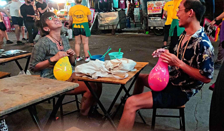 Lachende mensen op straat met buckets en lachgasballonnen in Khaosan, Bangkok