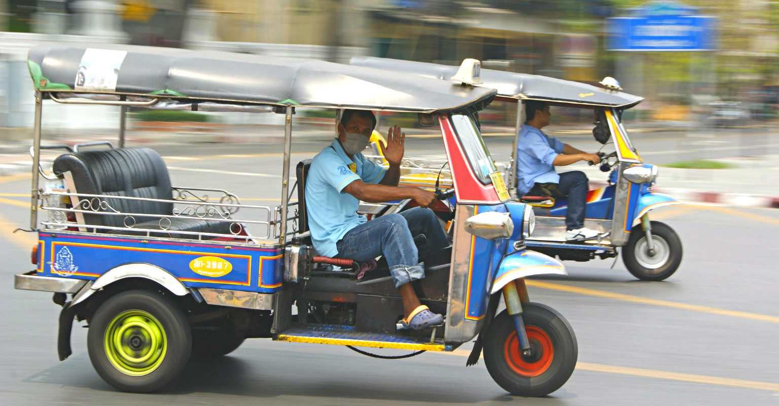 A tuk tuk driver waving at the camera