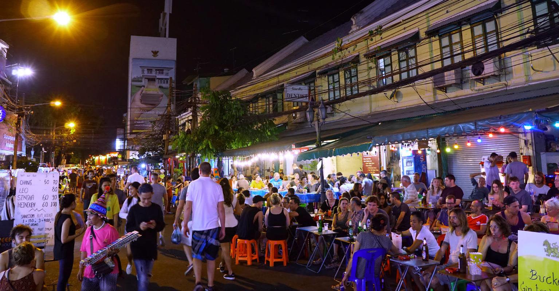 Mensen aan tafeltjes op straat van Rambuttri Road, Bangkok