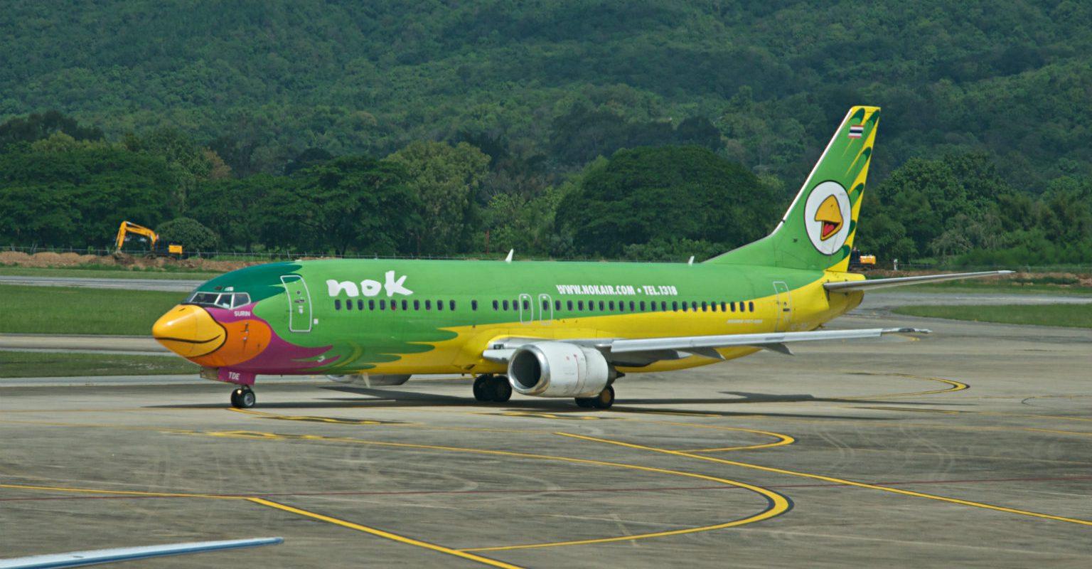 Vliegtuig van vliegtuigmaatschappij Nok Air beschildert als kleurrijke vogel op het vliegveld