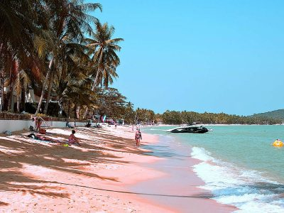 Maenam Beach, A Few People Lie On The Golden Yellow Elongated Beach Lined With Palm Trees.
