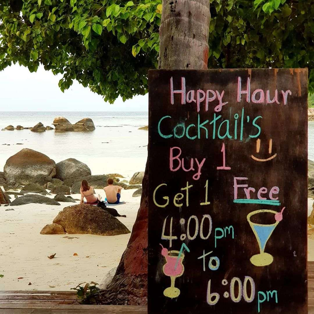 Sign with Happy Hour on the beach at Ten Moons Restaurant (one of the Best restaurants on Koh Lipe)