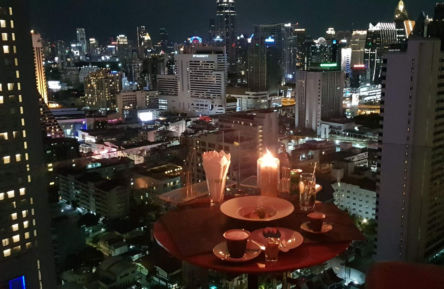 View of the skyline of Bangkok in the evening with a cup of coffee and dessert at Above Eleven Rooftop Bar