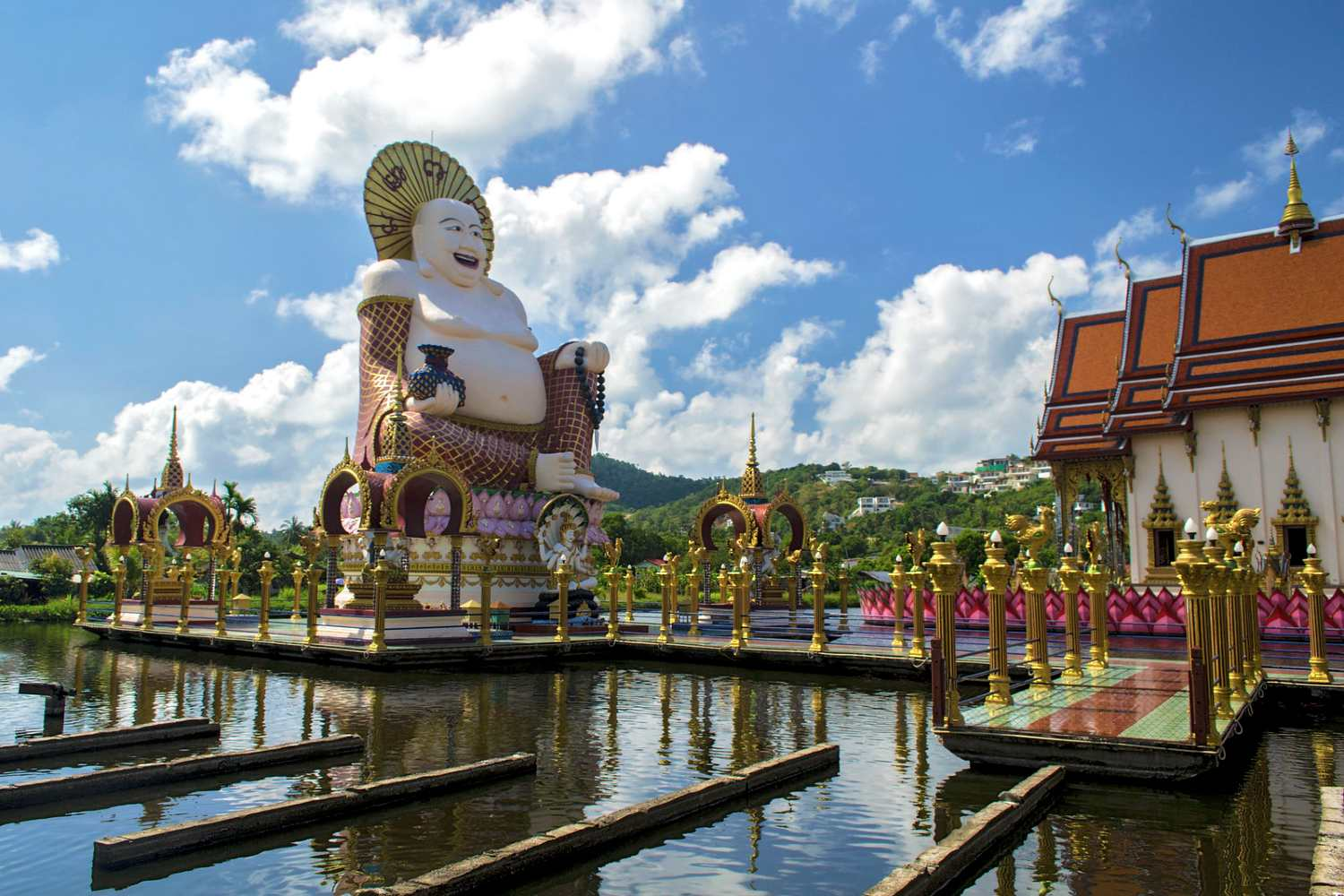 The pond and the laughing Buddha on the temple complex of the Wat Plai Laem on Koh Samui
