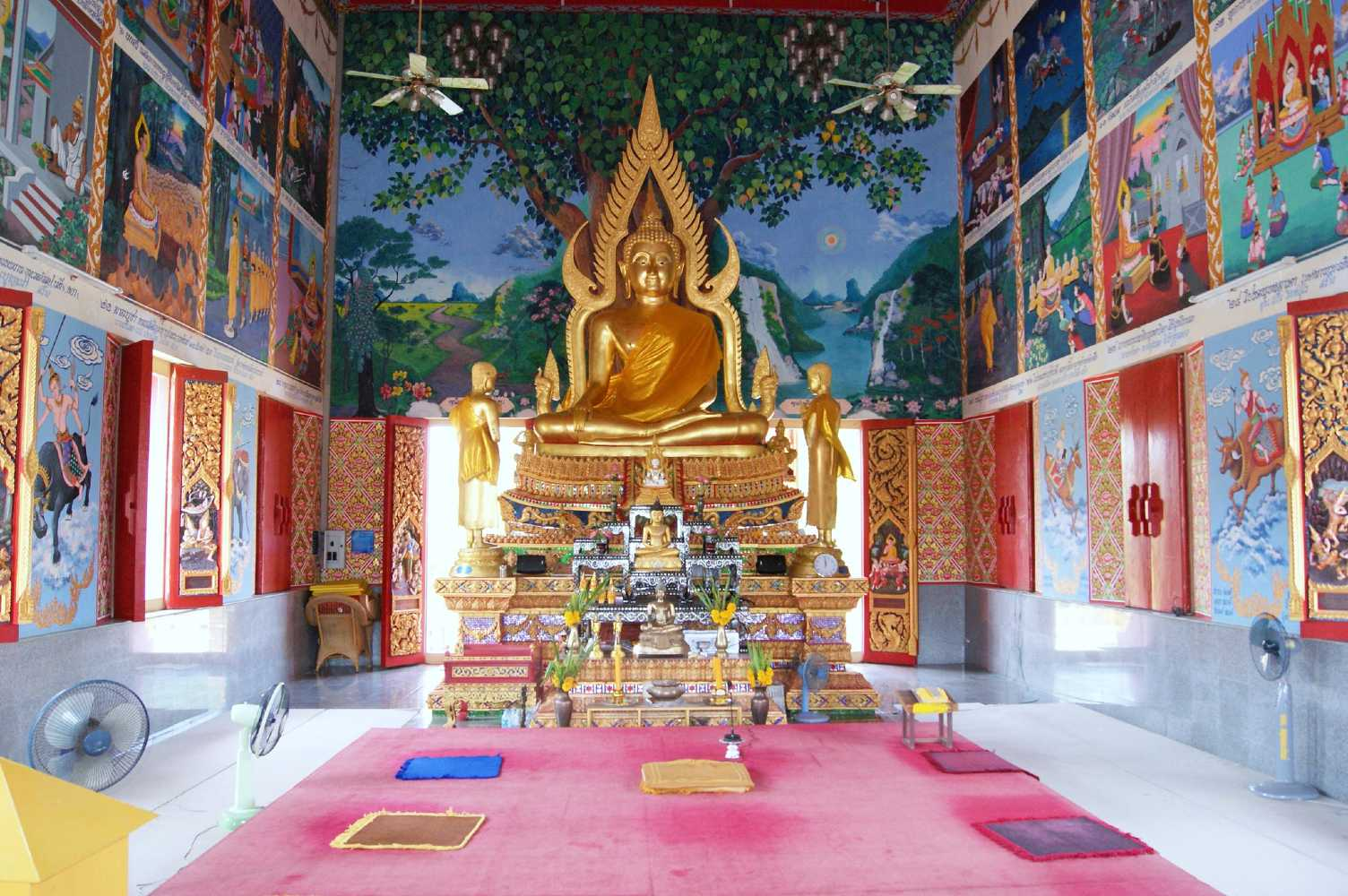 Golden Buddha inside the Wat plai Laem Temple with pictures on the wall of Buddha's life lessons