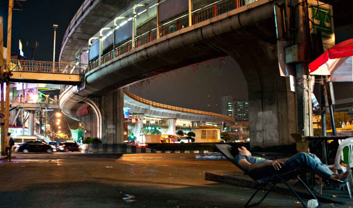 sky walk Victory Monument, met daaronder een man slapend in een stoel.