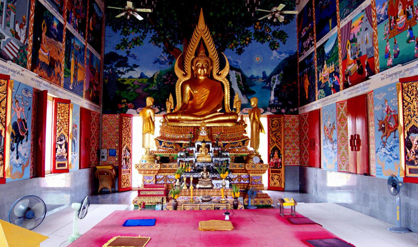 Gouden Buddha binnen in de Wat plai Laem Tempel met afbeeldingen aan de muur van de levenslessen van Buddha