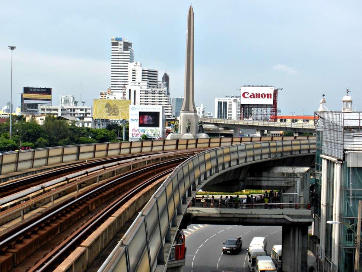 BTS en sky walk bij het Victory met op de achtergrond de pilaar van Victory Monument in Bangkok, Thailand.