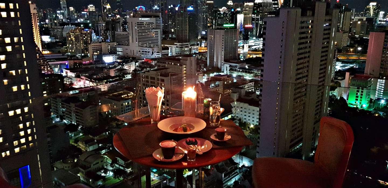 Above Eleven, tafeltje aan de glazen balustrade met weids uitzicht over de verlichte sky line van Bangkok, Thailand