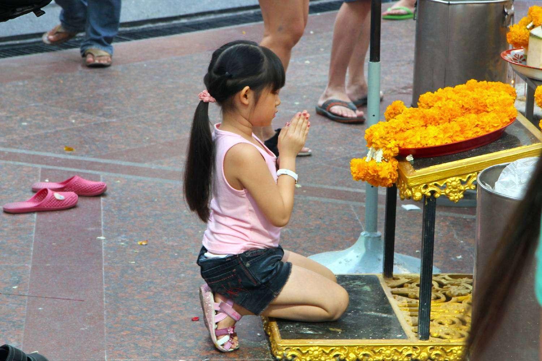Biddend kindje voor de Erawan Shrine in Bangkok, Thailand
