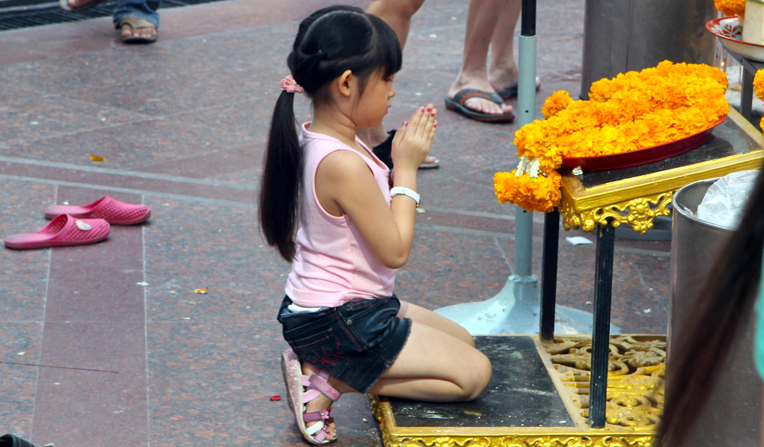 Biddend kindje voor de Erawan Shrine in Bangkok, Thailand
