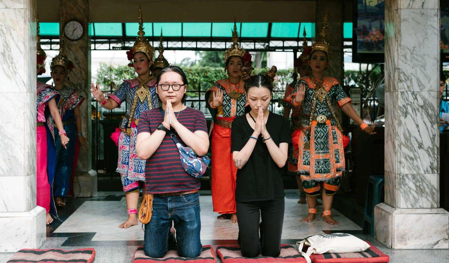 Biddende mensen die een geluksdans hebben gekocht bij de Erawan Shrine in Bangkok, Thailand