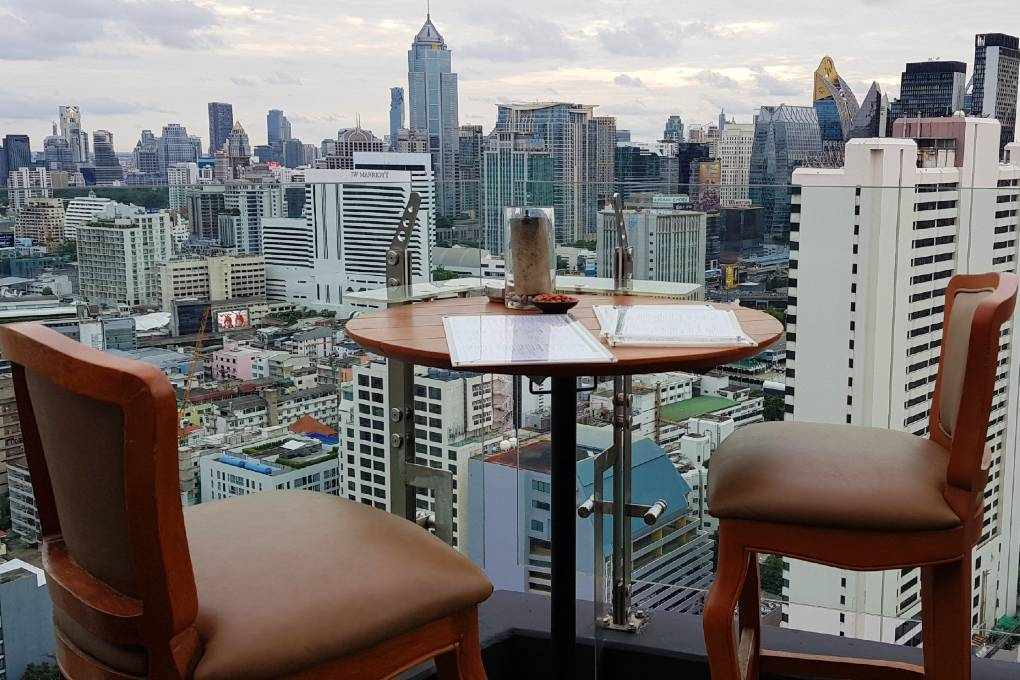 Table for 2 persons long glass balustrade overlooking the sky line of Bangkok, near Above Eleven in Thailand.