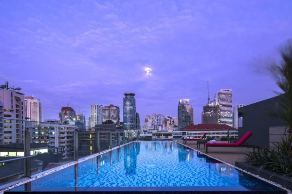 Swimming pool of the Travelodge hotel with in the background the skyline of Bangkok in Thailand