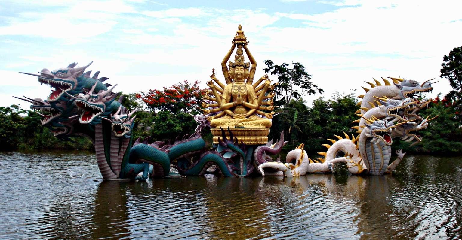 Fontijn met drakenkoppen en Boeddhabeeld in het water van Ancient City. Muang Boran, Thailand