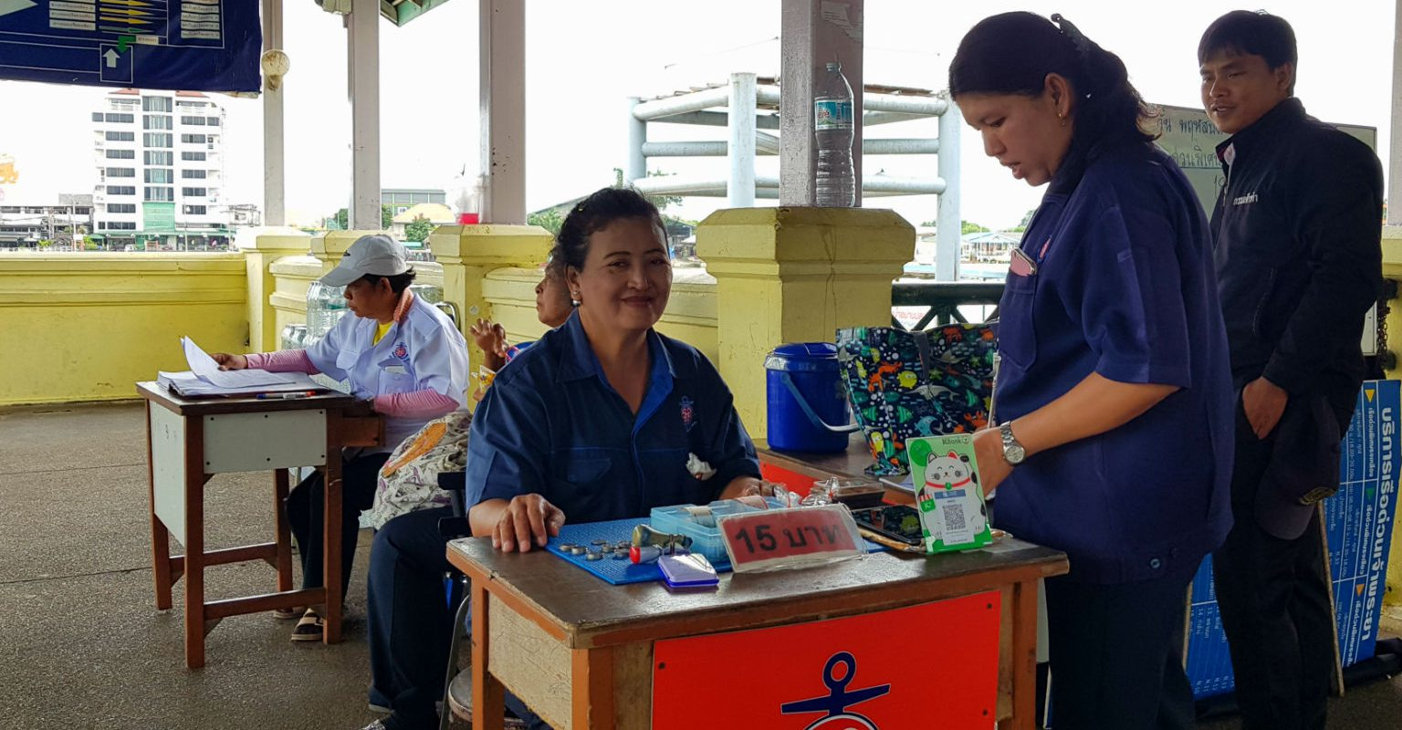 Friendly card seller of the Chao Phraya River boat in Bangkok, ticket 15 bath for the boat with orange flag.