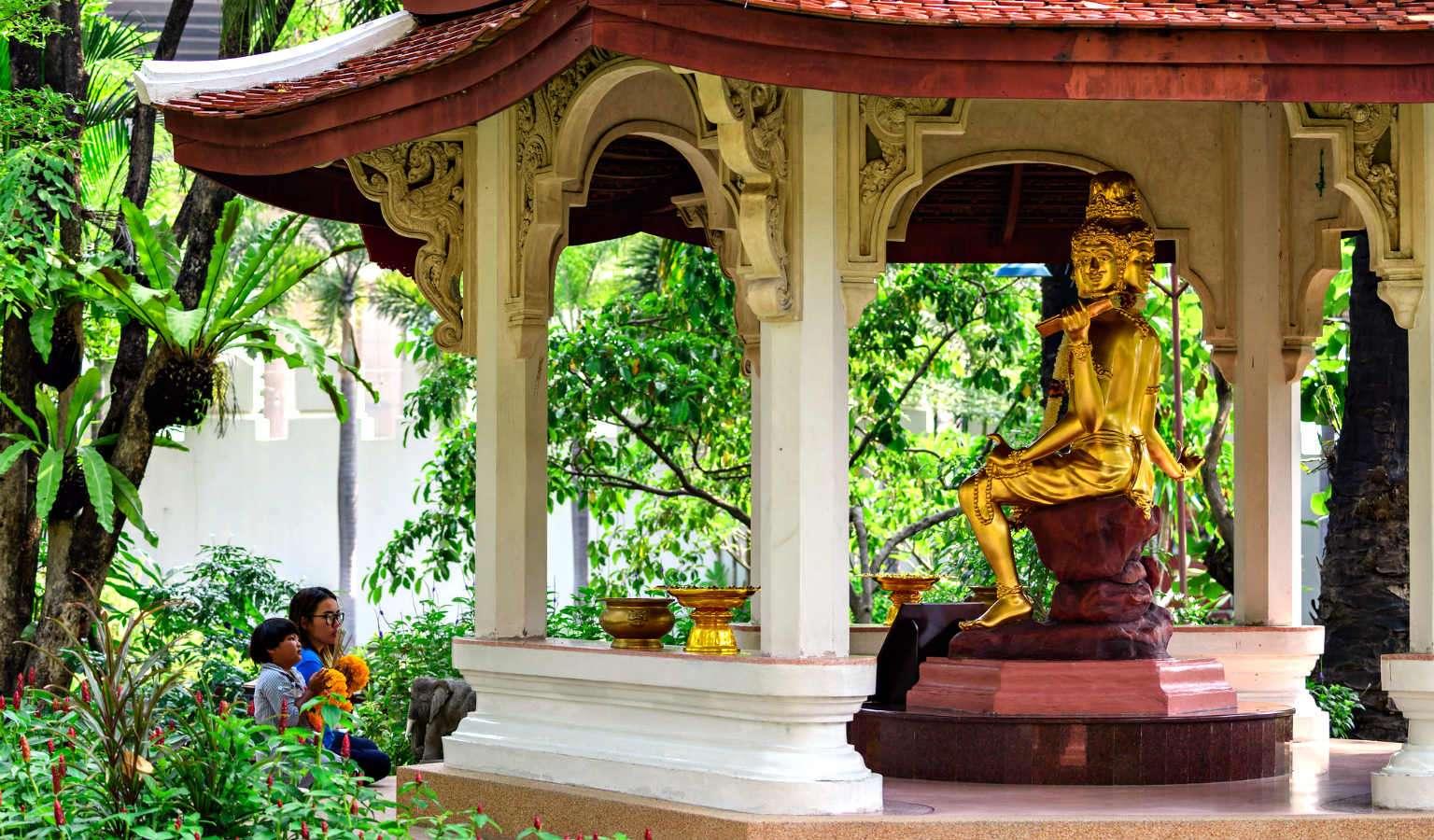 schaduwrijke sprookjesachtige tuin met bruggetjes en bijzondere beelden in de tuin van het Erawan Museum in Bangkok zoals van de god Phra Phrom