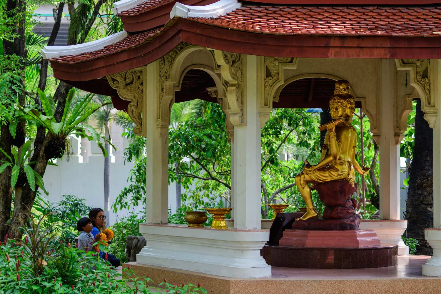 Shady fairytale garden with bridges and special statues in the garden of the Erawan Museum in Bangkok like of the god Phra Phrom