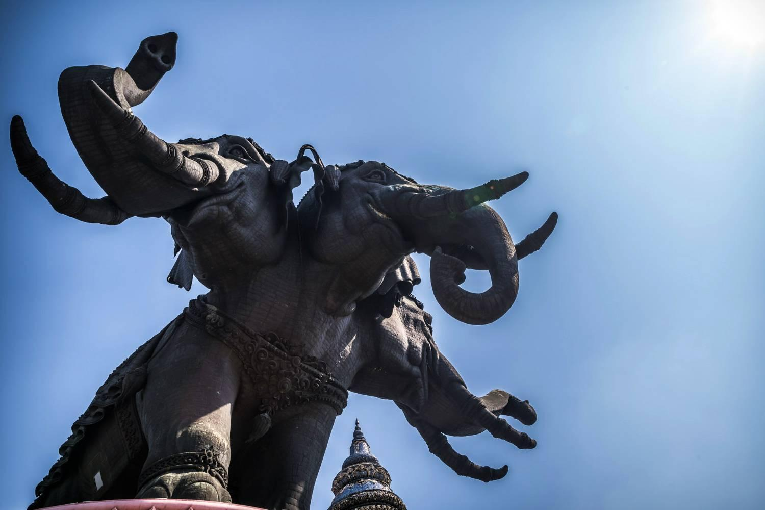 three-headed elephant from the Erawan Museum in Bangkok depicted against a blue sky.