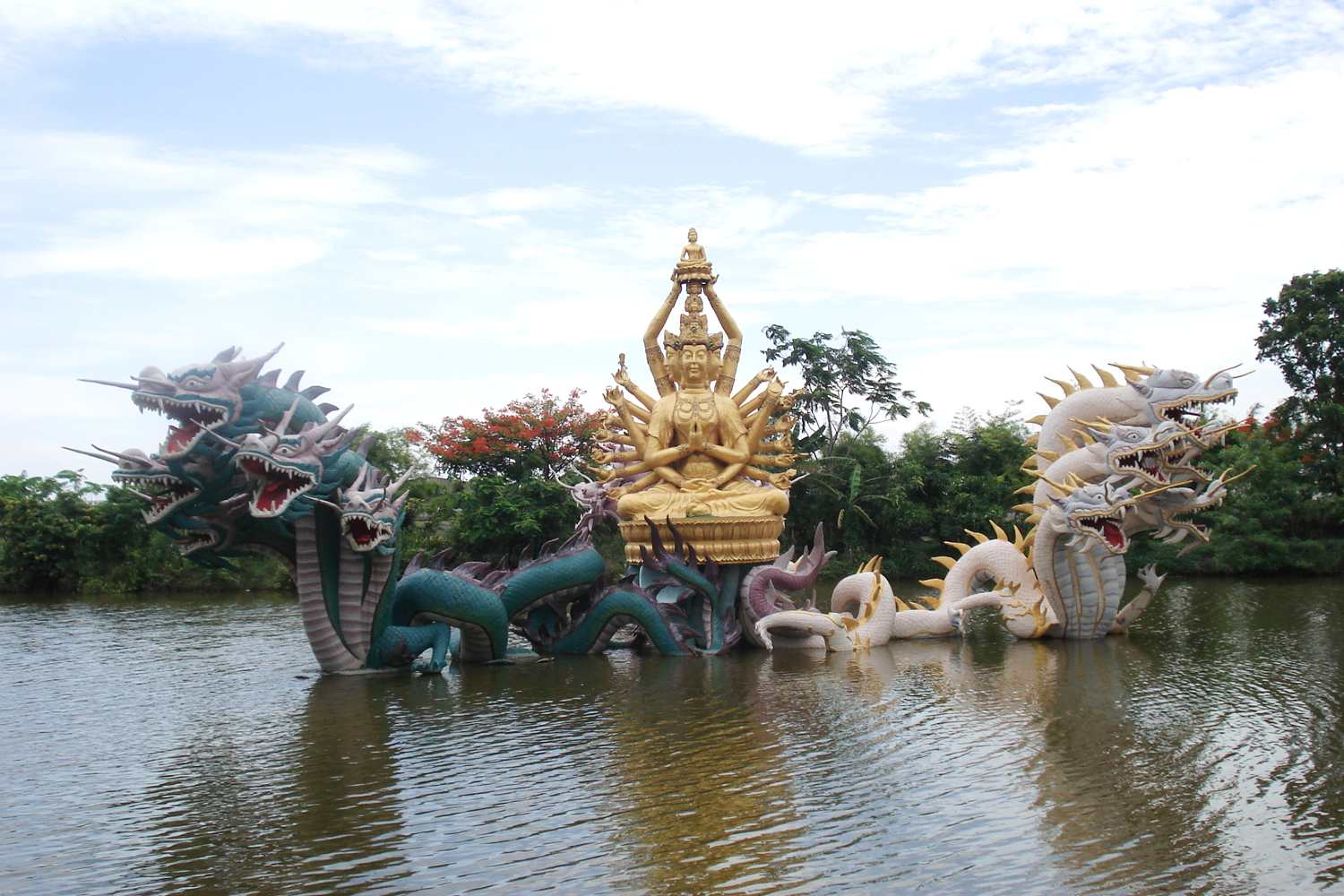 Fountain with dragon heads and Buddha statue in the waters of Ancient City. Muang Boran, Thailand