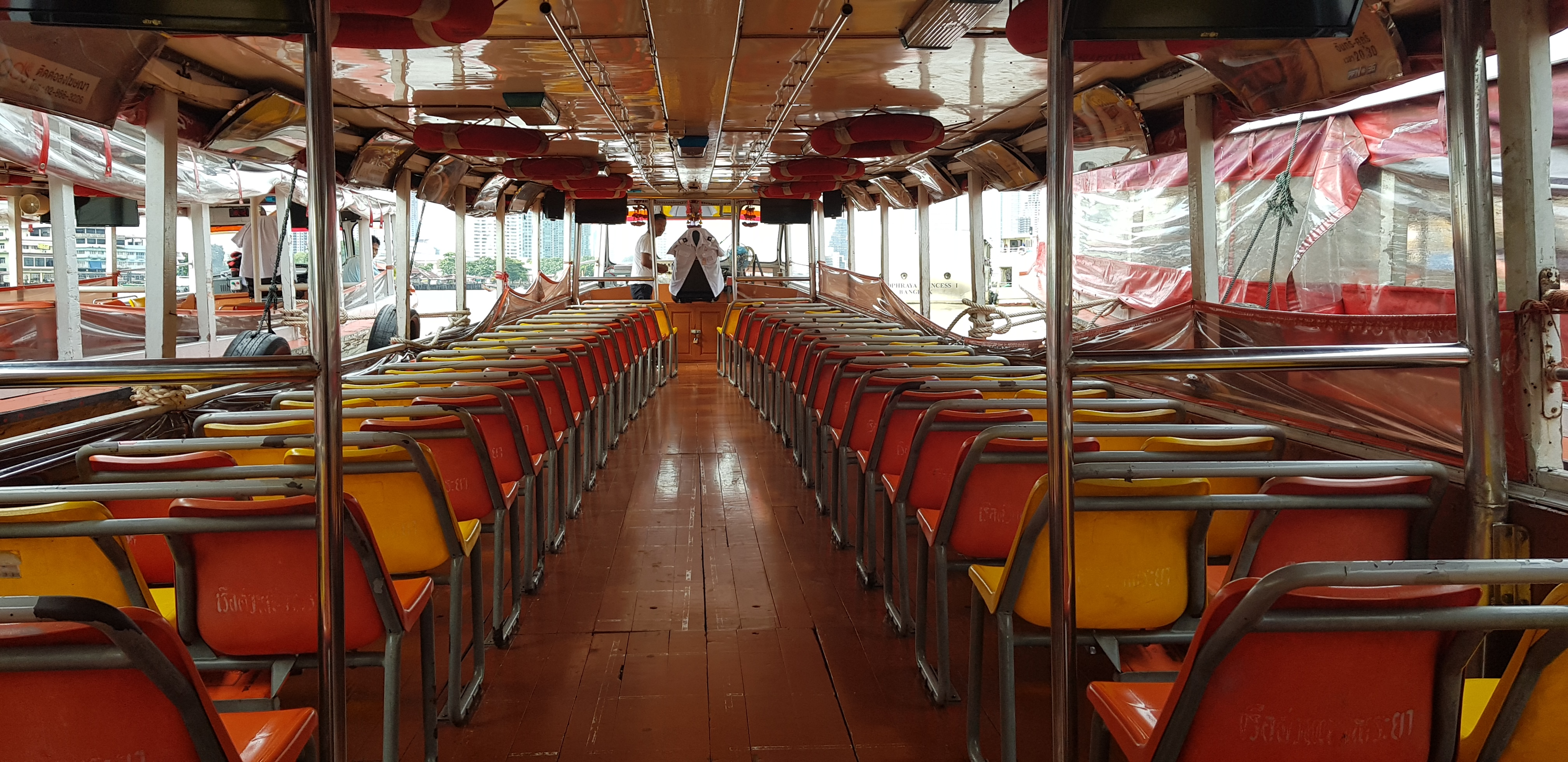 rows of chairs on the inside of the Chao Phraya Express boat
