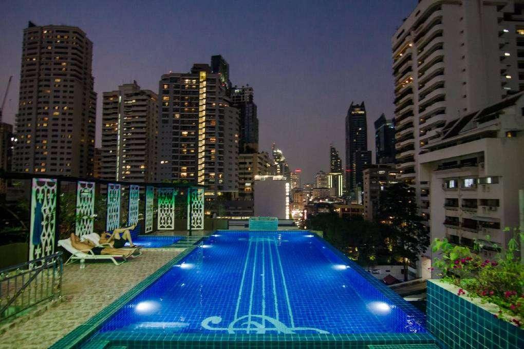 Het zwembad in de avond van Hope Land Hotel Sukhumvit 8 in het Nana gebied van Bangkok