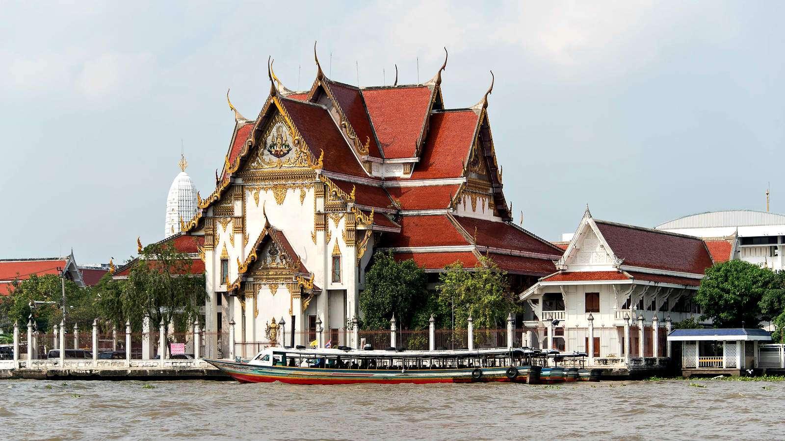 witte tempel met rood dak, op de voorgrond de Chao Phraya rivier