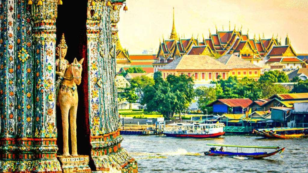 Grand Palace van Bangkok, met gouden en rode daken gezien van de overkant van de Chao Phraya rivier