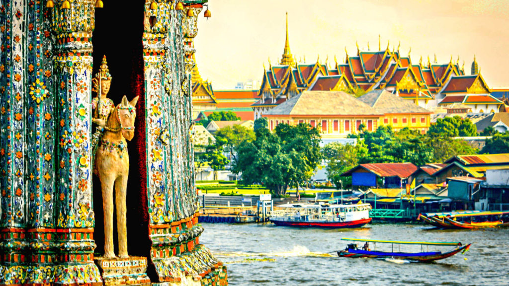 Grand Palace, met gouden en rode daken gezien van de overkant van de rivier