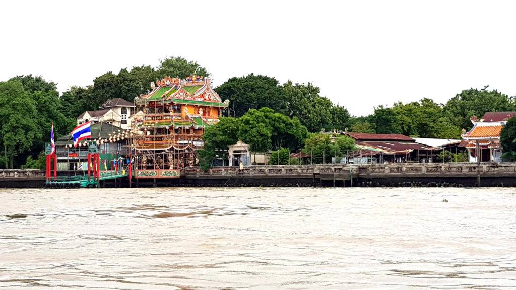 Temple made of wood and decorated with carvings, with in the foreground the Chao Phraya River
