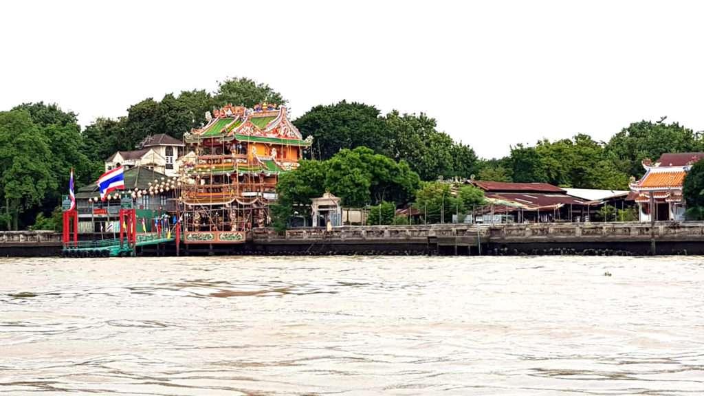 Tempel gemaakt van hout en versierd met houtsnijwerk, met op de voorgrond de Chao Phraya Rivier