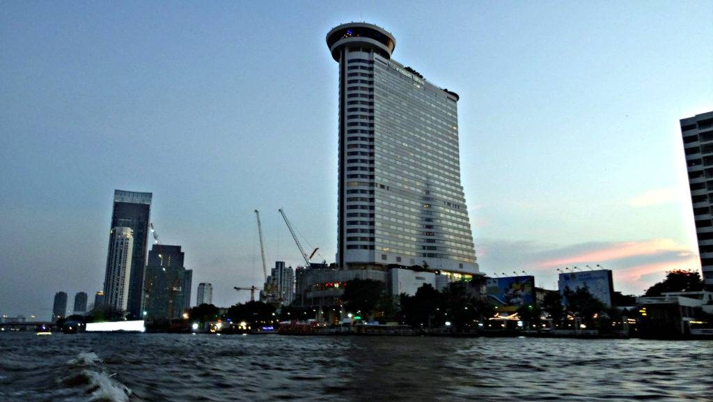 Hoog grijs gebouw met bovenop een UFO vormig gebouw (Millennium Hilton Bangkok). op de voorgrond de Chao Phriya Rvier van Bangkok