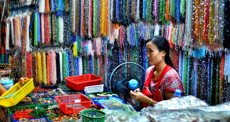 Chinatown, Phahurat Market (Little India) Verkoopster met gekleurde kralenkettingen.