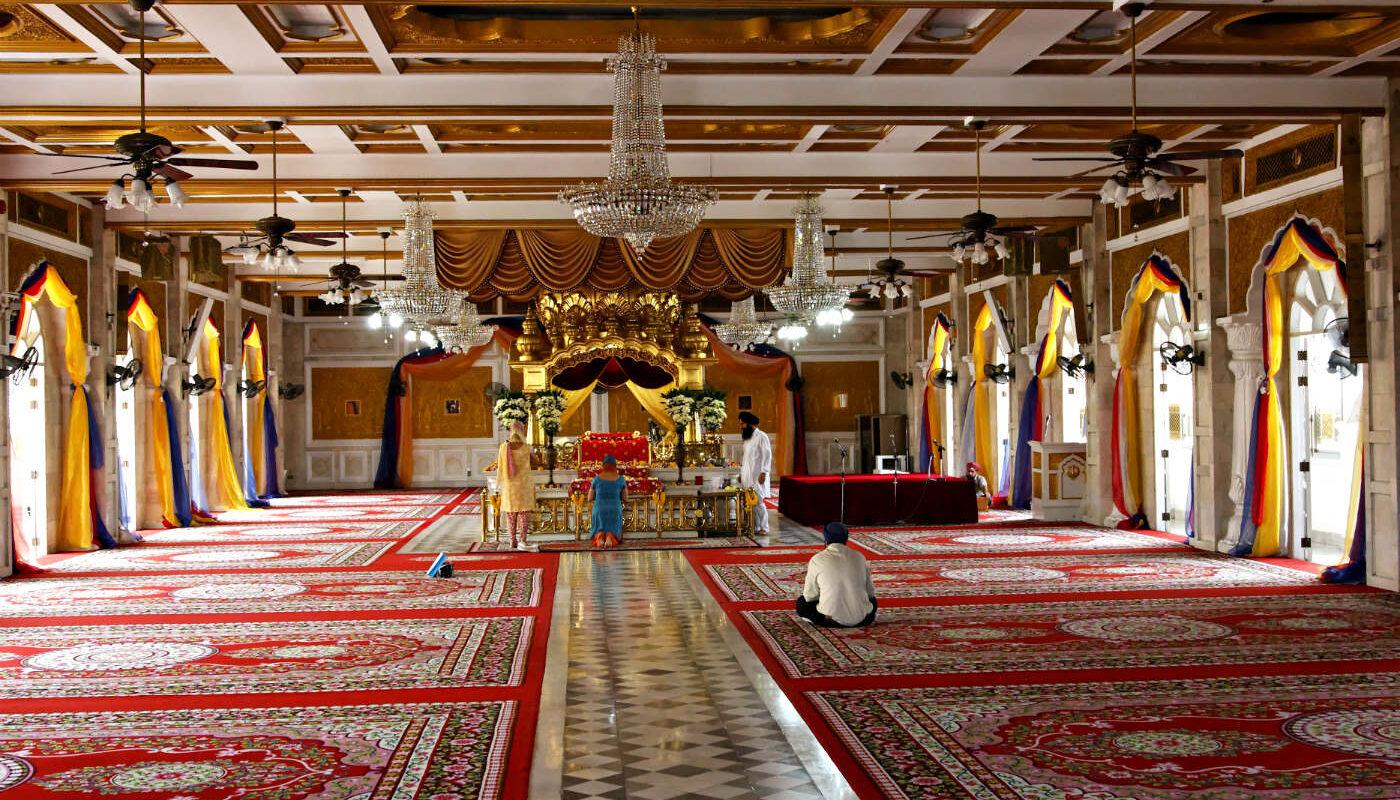 Grote ruimte met rode Perzische tapijten en biddende mensen bij het alter van de Sikh Tempel, Gurudwara Sri Guru Singh Sabha Tempel in China Town