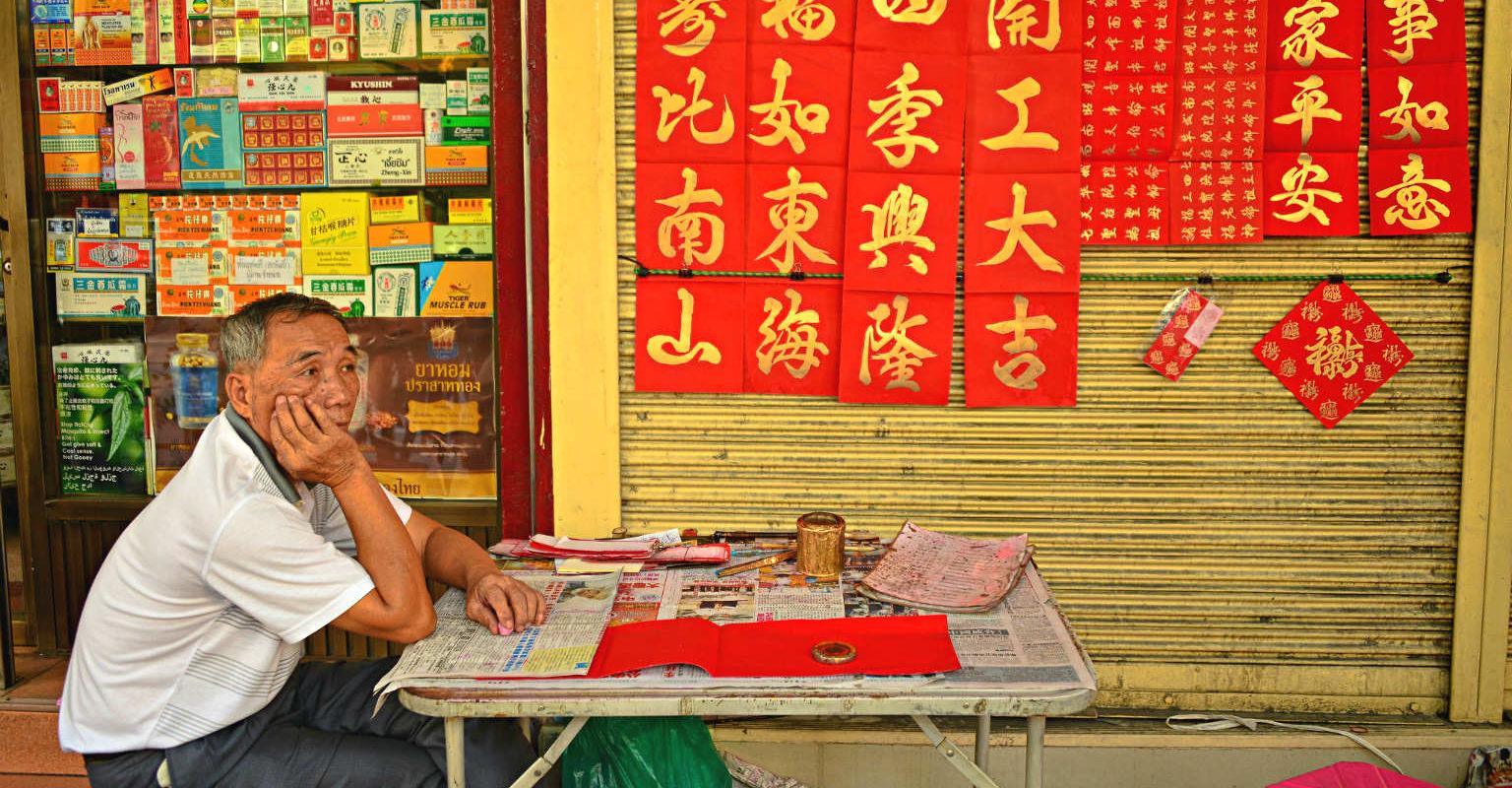 Chinatown/ Yaowarat Road, Chinese man zit aan tafeltje met een krant voor een apotheek shop.
