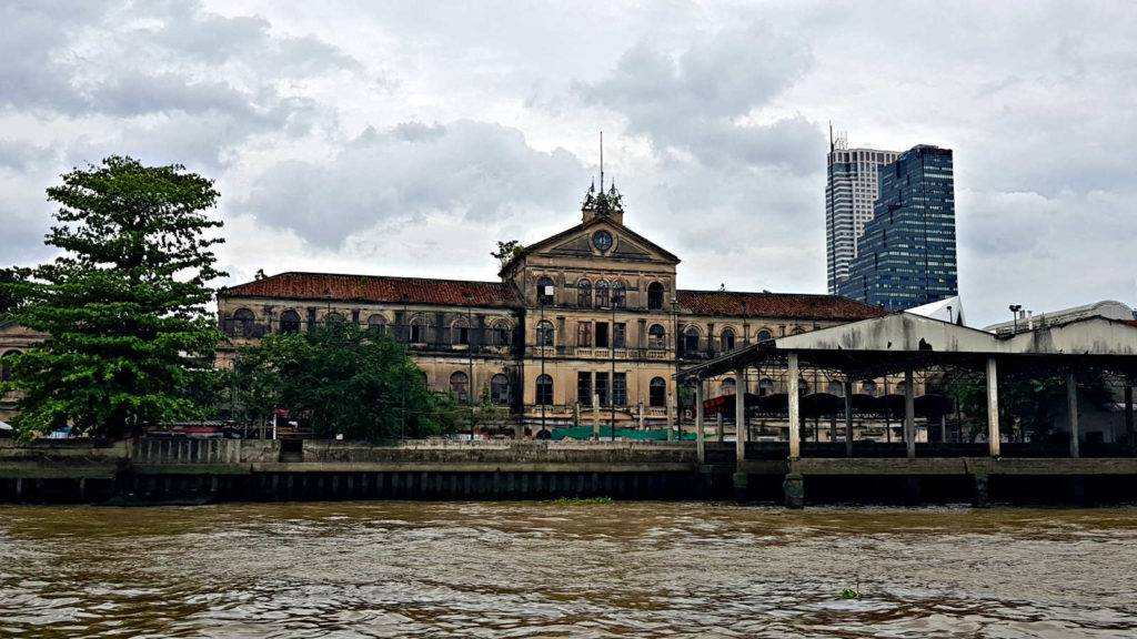 Expired building of 3 floors with a tower on the Chao Phraya River in Bangkok.