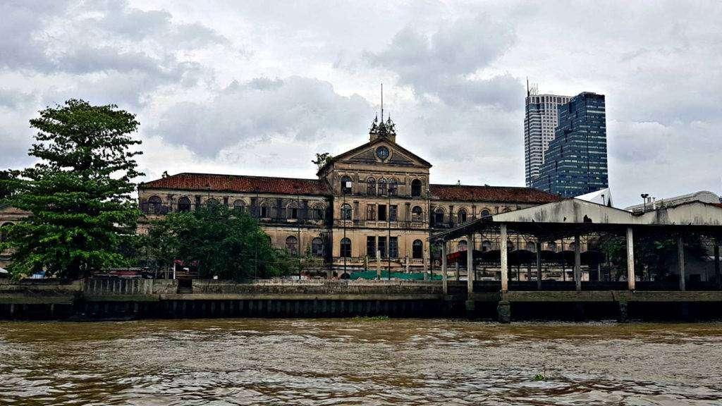 Vervallen gebouw van 3 vediepingen met een toren aan de Chao Phraya Rivier in Bangkok