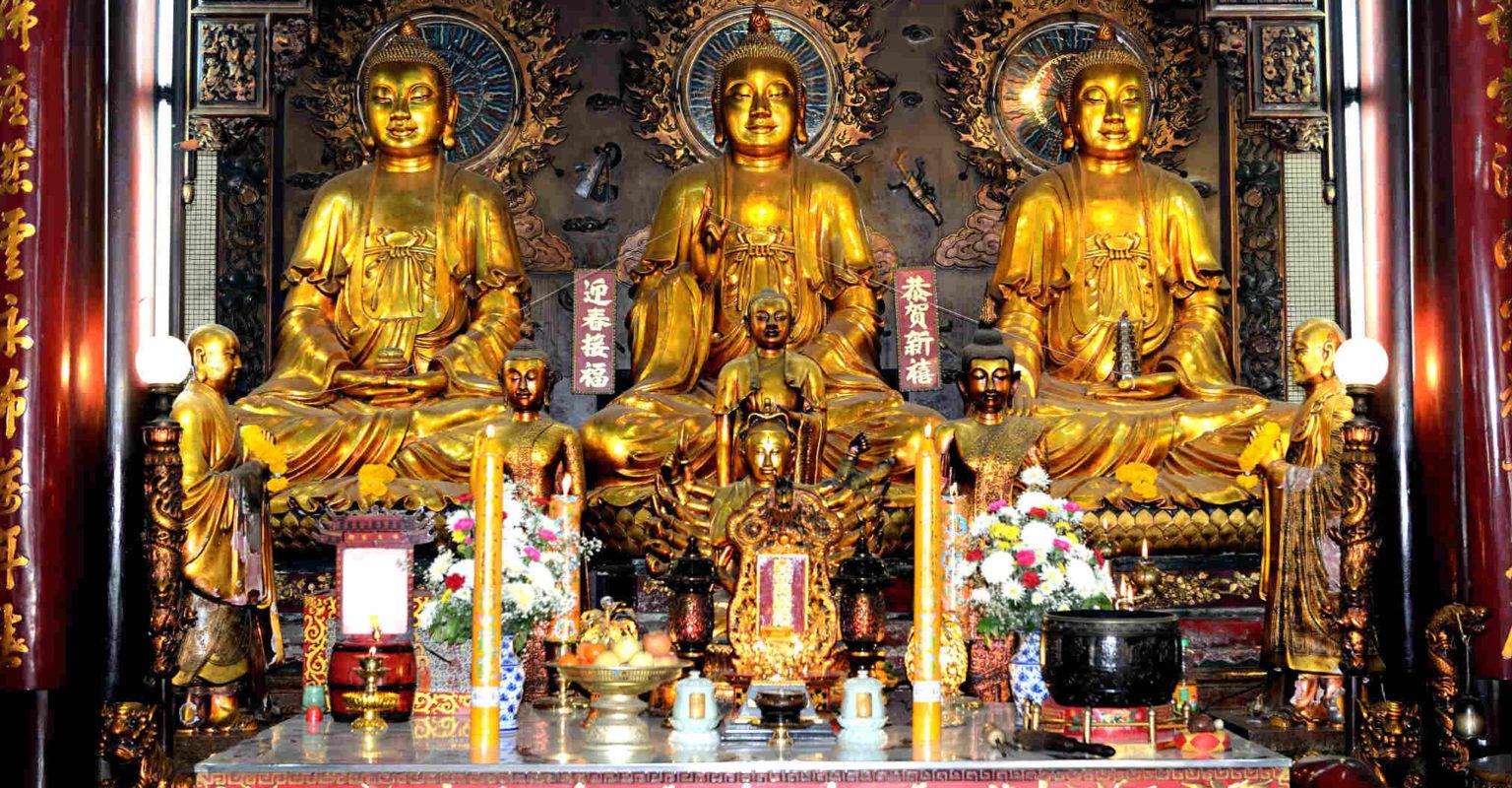 3 goudkleurige Boeddha's naast elkaar op een verhoging in de tempel Wat Mangkon Kamalawat in Chinatown, Bangkok