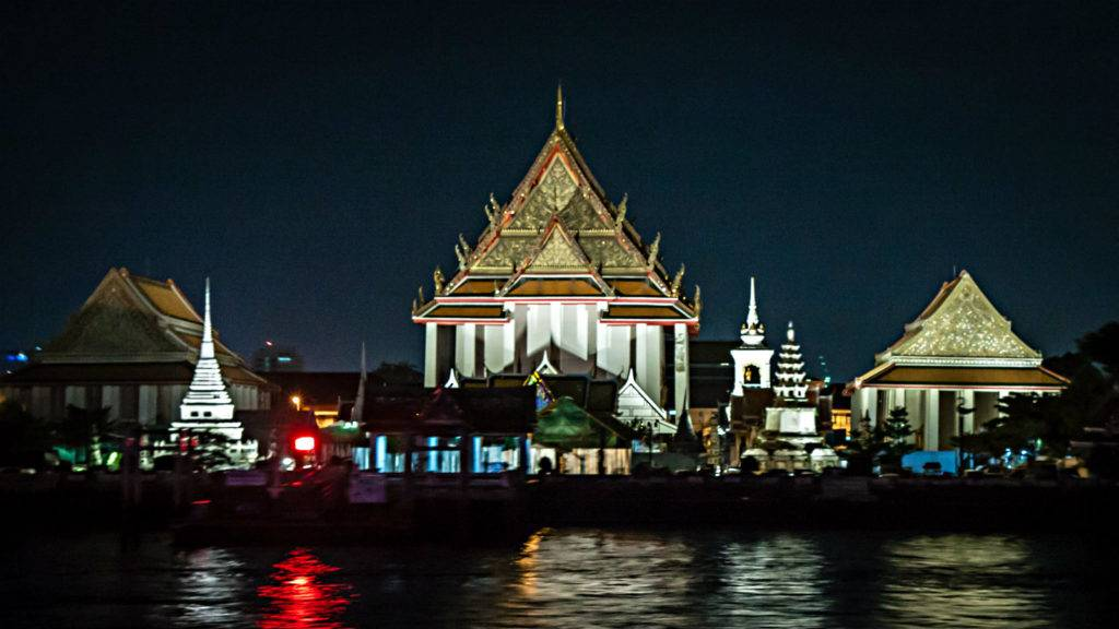 Some Kalayanamitr, white temple with golden roofs lit with lamps in the dark, in the foreground the Chao Phraya River of Bangkok.