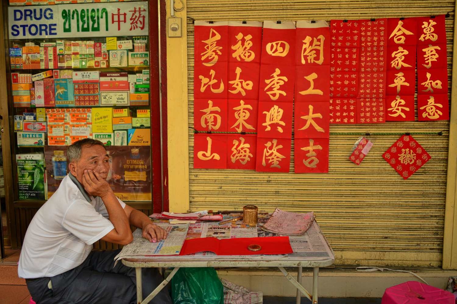 Chinese man sits at a table with a newspaper in front of a pharmacy in ChinaTown, Bangkok