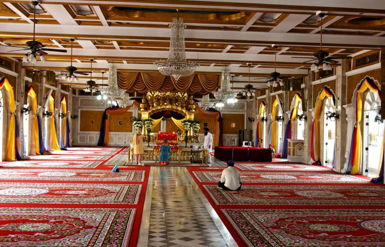 Large room with red Persian carpets and praying people at the alter of Sikh Temple, Gurudwara Sri Guru Singh Sabha Temple in China Town.
