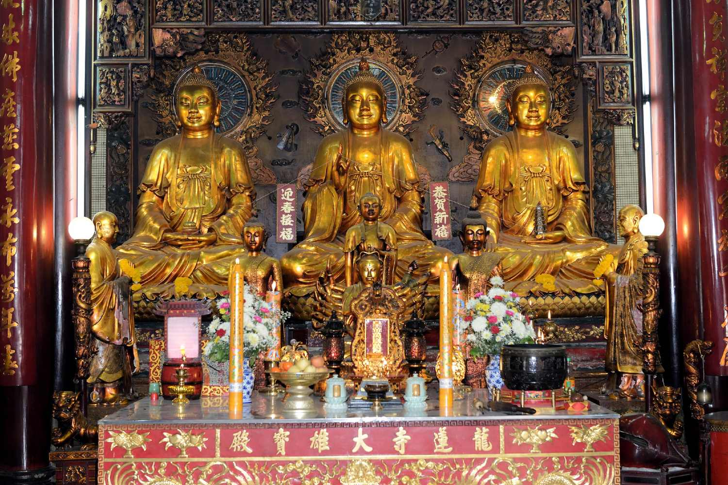 3 golden Buddha's side by side on an elevation in the temple Wat Mangkon Kamalawat in Chinatown, Bangkok