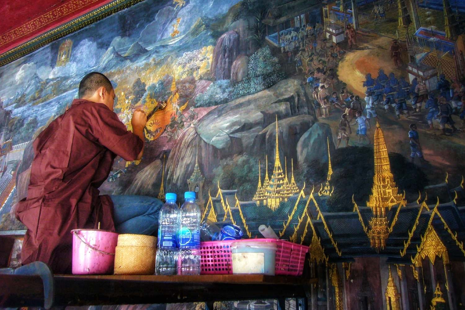 Monk is updating a wall drawing of the Grand Palace