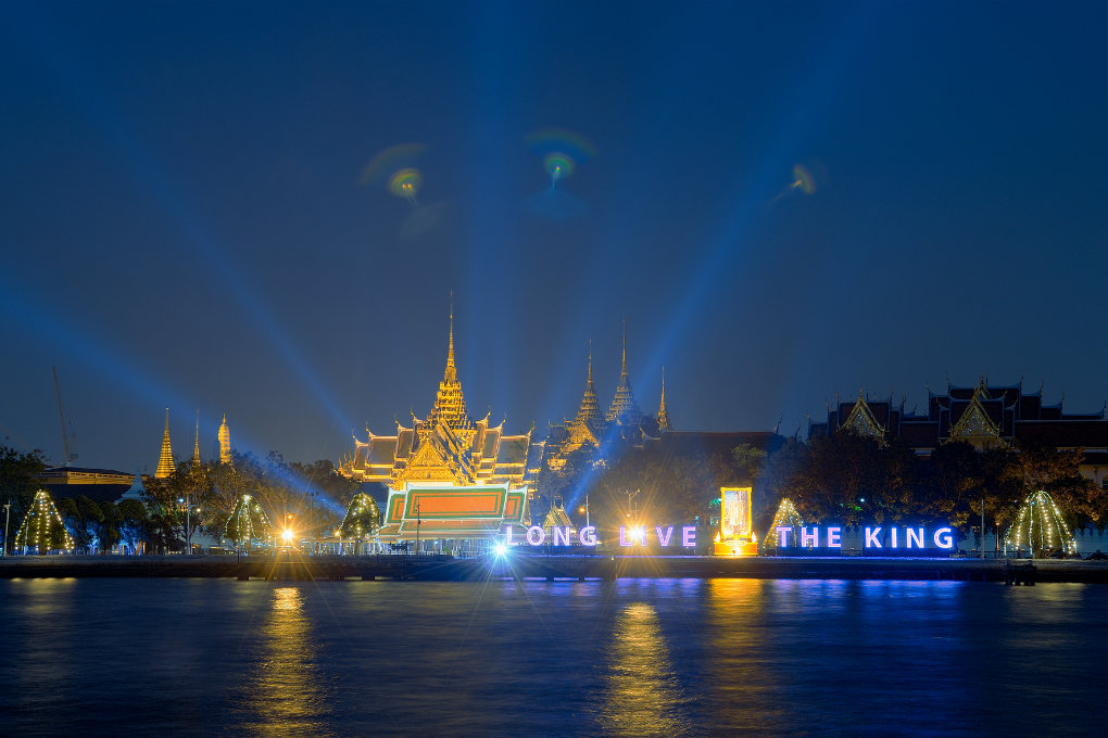 The Grand Palace in Bangok, Thailand in the evening from across the Chao Phraya River