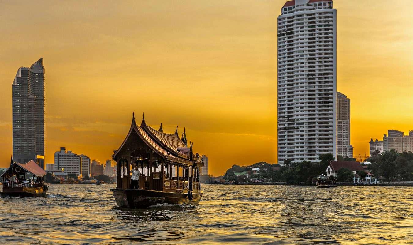 Boot op de Chao Phraya Rivier in Bangkok tijdens zonsondergang.