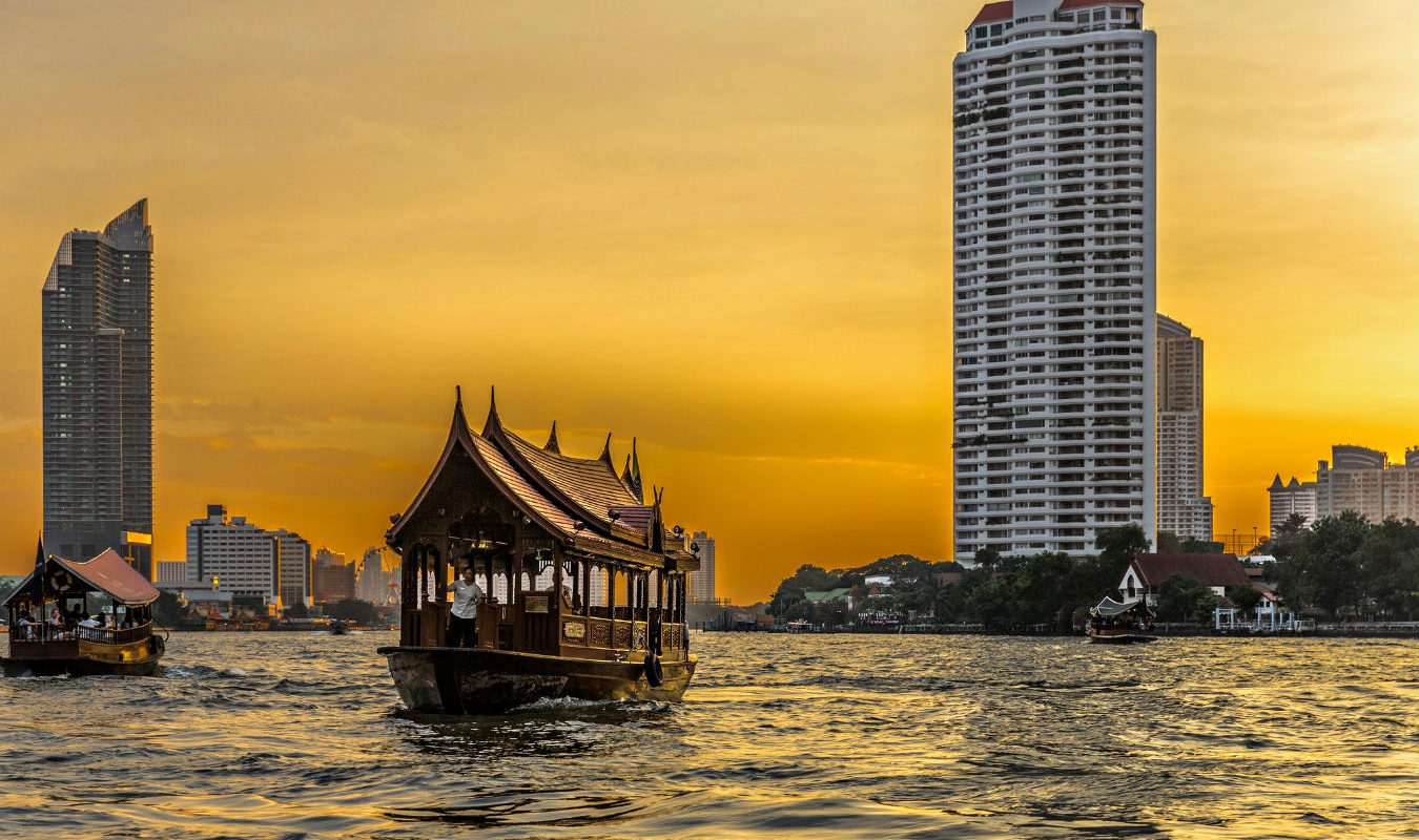 Boat on the Chao Phraya River in Bangkok at sunset.
