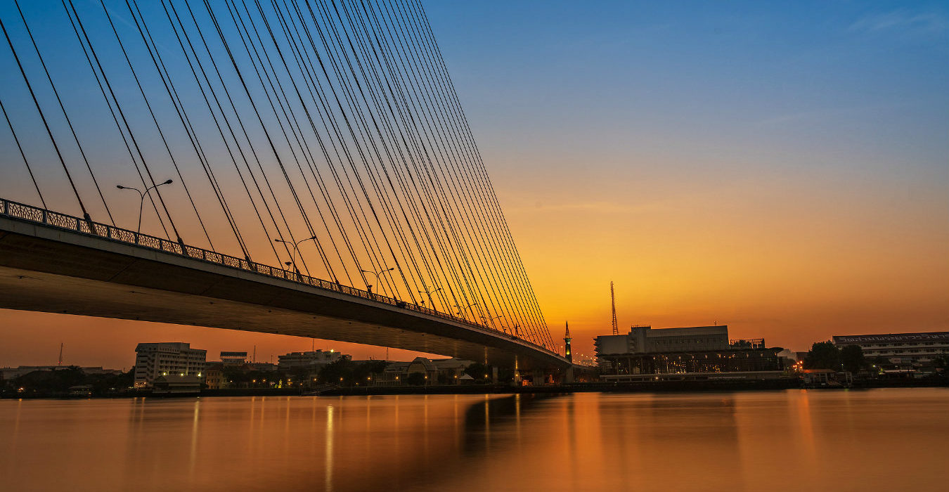 Rama VIII Bridge over de Chao Phraya Rivier tijdens zonsondergang