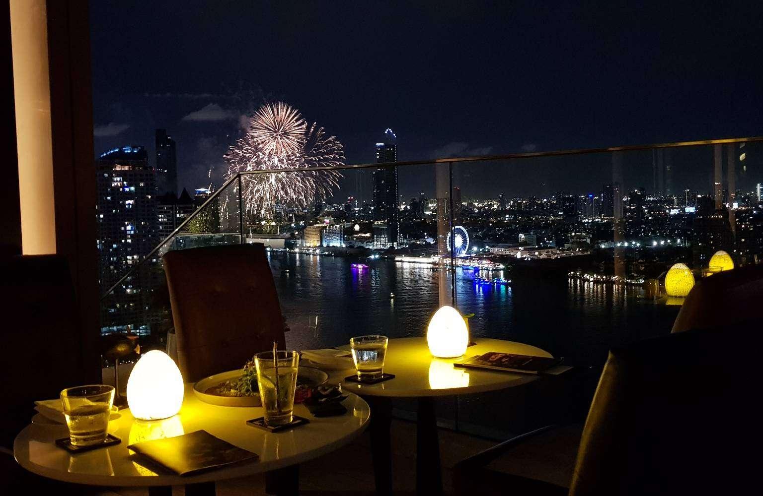 SEEN Sky Bar at Avani+ Riverside Bangkok Hotel with views of the Chao Phraya River and fireworks.