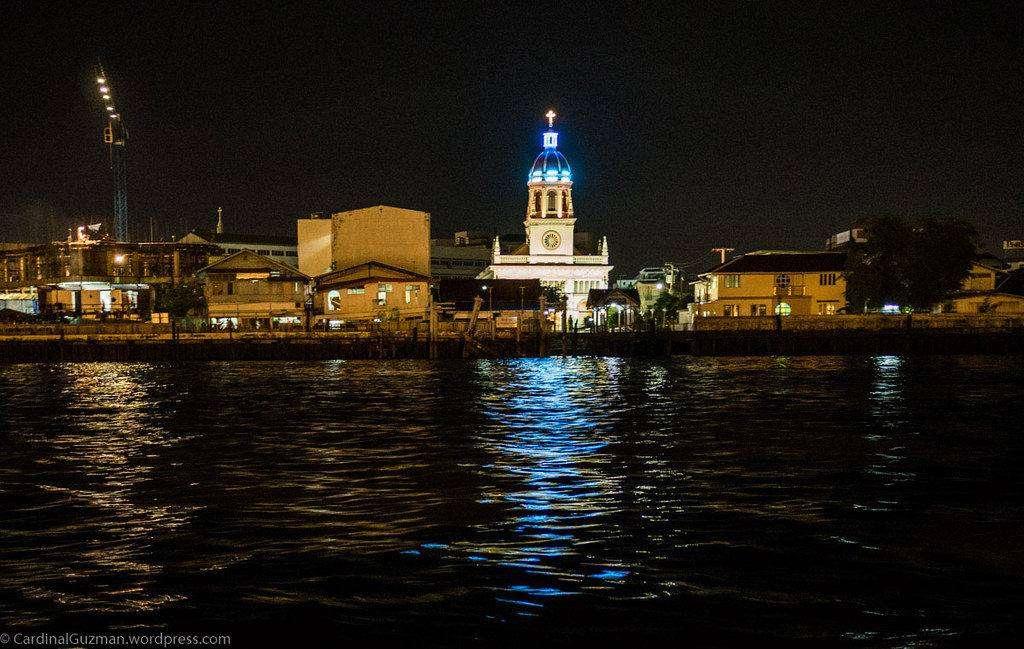 small church (Santa Cruz Church) beautifully illuminated in the dark as seen from the Chao Phraya River in Bangkok